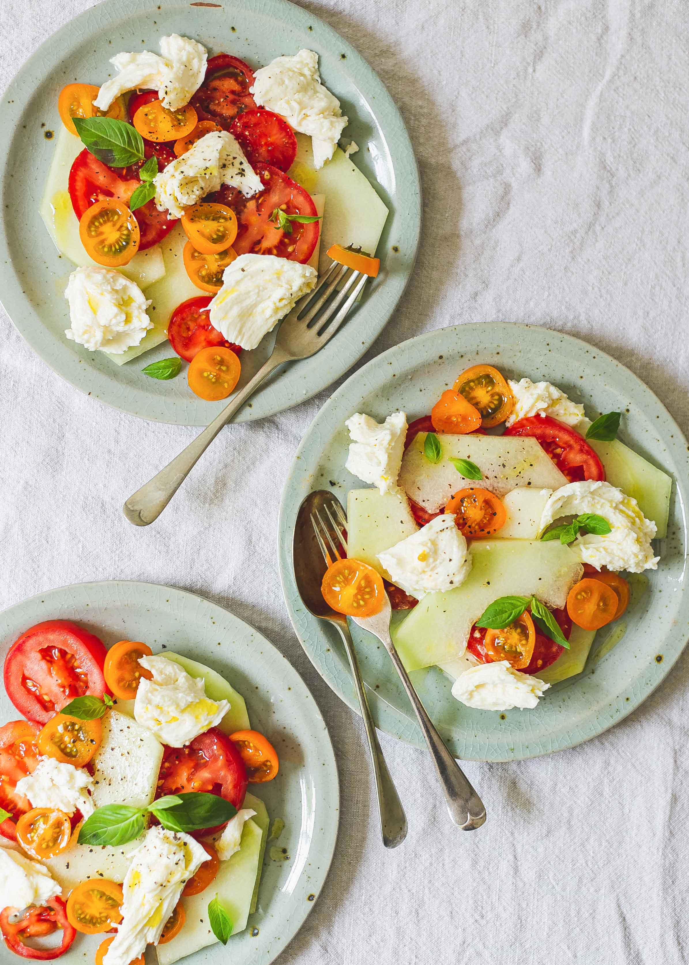 Three plates of melon, tomato and moz salad