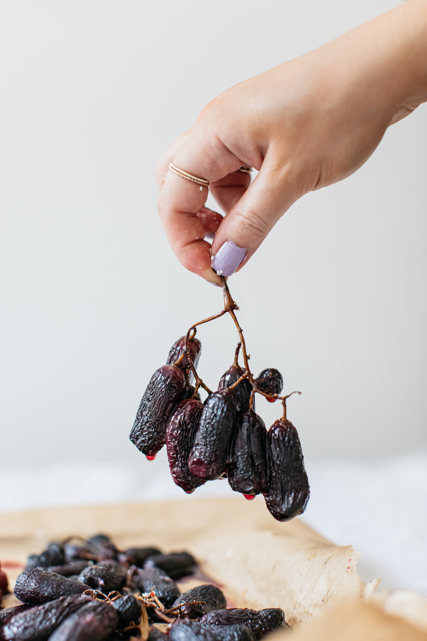 Hand holding roasted grapes