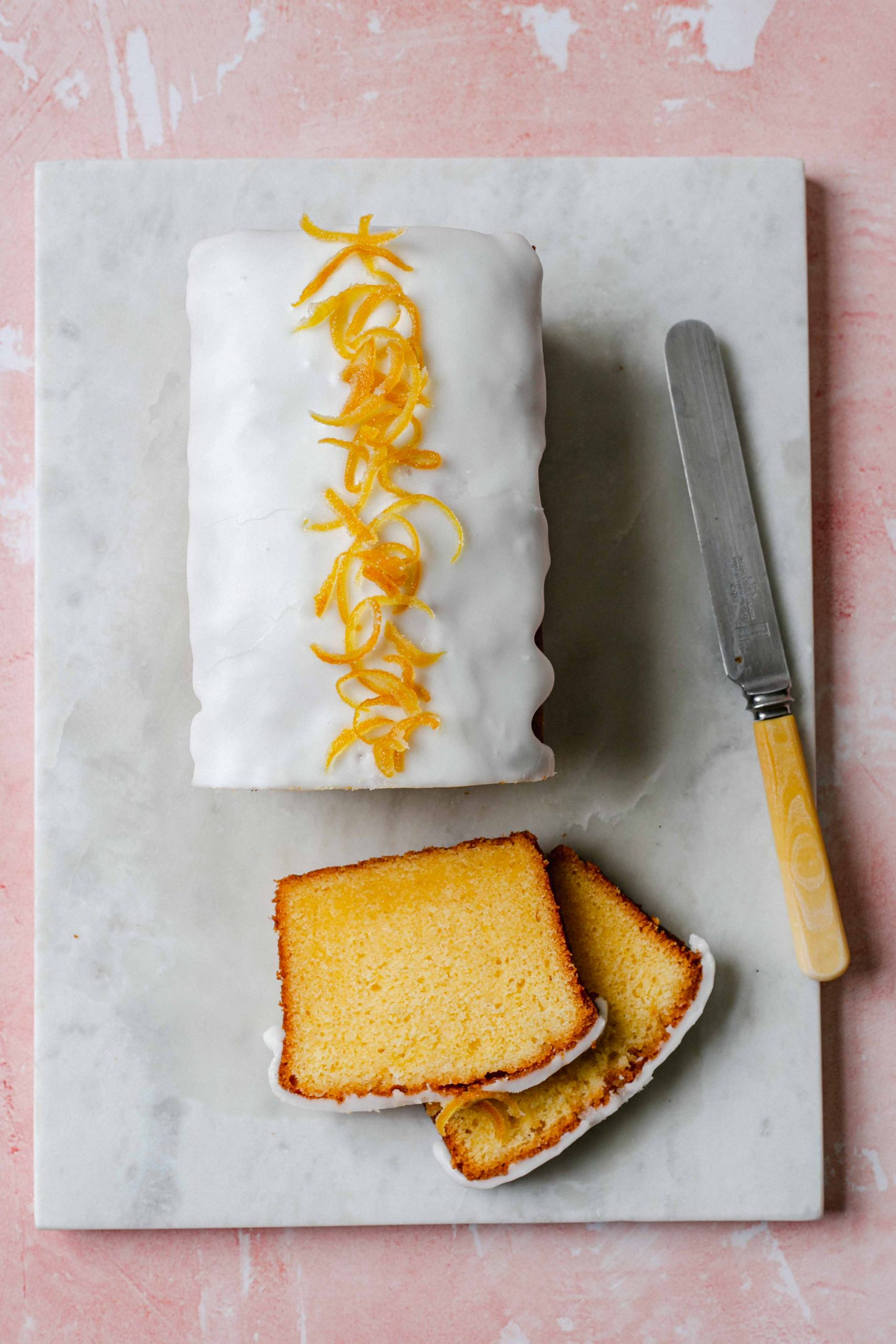 Pink background with slices of lemon drizzle cake